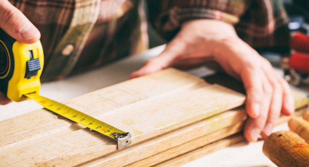 En snickare mäter ut trall som ska användas vid ett altanbygge.