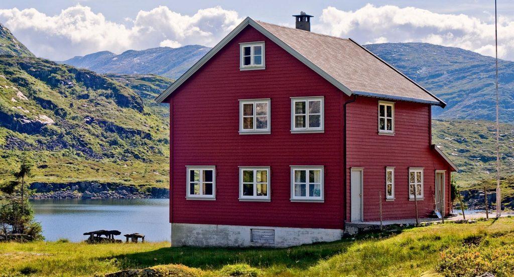 Ett rött fritidshus vid en sjö.
